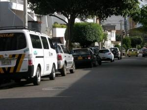Carros estacionados a lado y lado de la vía en la 48.