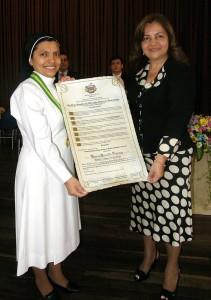 La hermana rectora Yanira Carrillo Figueroa recibe de manos de Martha Montero la condecoración.