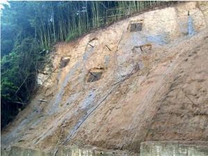 Perfilado del talud, instalación de drenes, anclajes y parrillas alrededor de los anclajes. Proceso constructivo.