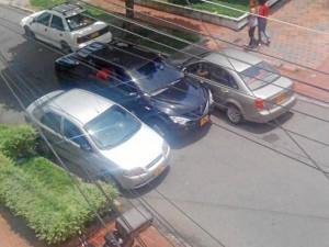 """@Berracol y @juanframejia nos enviaron estas dos fotos de carros estacionados entre el andén y la vía, en la carrera 35A con calle 52. """"Y eso que está prohibido parquear ahí…""""."""