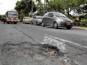 En la vía hay otros huecos que ponen en peligro la vida de motociclistas y hasta peatones. Este es llegando al semáforo.