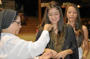 El colegio obsequió a cada estudiante una medalla como detalle por sus 15 años.