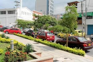 Además de invadir la vía con estacionamiento de carros, también se ven los andenes ocupados.