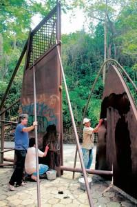 Dos personas trabajan en la restauración de la escultura de la Unab.