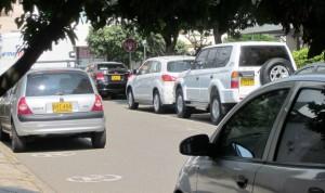 Se observan carros estacionados a lado y lado de la vía del barrio Las Mercedes