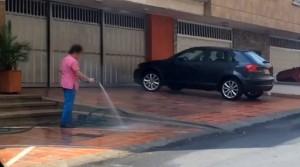 Con una manguera, una vecina de Cabecera lava un andén, acto que reprocha un vecino del sector. - Suministrada /GENTE DE CABECERA